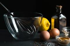 Huevos, aceite de oliva, mostaza en un fondo negro Foto de archivo