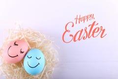 Huevos azules y rosados con sonrisas pintadas en la jerarquía, espacio de la copia Diseño feliz de la tarjeta de felicitación del imagen de archivo libre de regalías