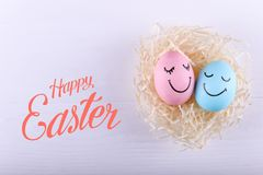 Huevos azules y rosados con sonrisas pintadas en la jerarquía, espacio de la copia Diseño feliz de la tarjeta de felicitación del imágenes de archivo libres de regalías