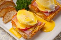 Huevos Benedicto en el pan con el tomate y el jamón Fotografía de archivo