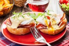 Huevos Benedicto en los molletes tostados con el jamón Foto de archivo libre de regalías