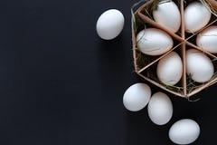 Huevos blancos del pollo fresco en cartón en fondo negro Foto de archivo