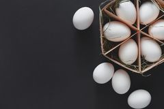 Huevos blancos del pollo fresco en cartón en fondo negro Imagen de archivo libre de regalías