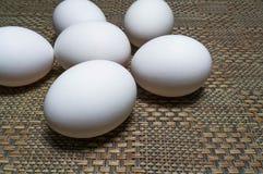 Huevos blancos en una tabla imagenes de archivo
