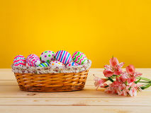 Huevos brillantemente coloreados con las flores en una cesta de mimbre Fotografía de archivo