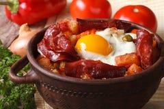 Huevos cocidos con el chorizo y las verduras en el pote horizontal imagen de archivo libre de regalías