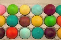 Huevos coloreados en cartón Foto de archivo libre de regalías