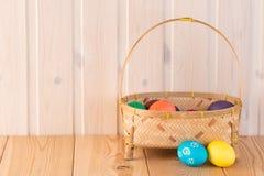 Huevos coloreados en una cesta de la paja Imagenes de archivo