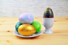 Huevos coloreados en una placa blanca en un backgrou borroso de madera natural Fotos de archivo