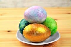 Huevos coloreados en una placa en un fondo de madera natural Fotografía de archivo