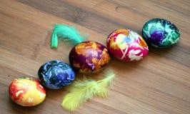 Huevos coloridos agradables en una tabla de madera Imagenes de archivo
