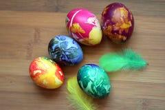Huevos coloridos agradables en una tabla de madera Fotos de archivo libres de regalías