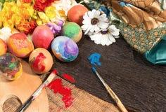 Huevos coloridos de Pascua con las flores de la primavera y los dos cepillos del pintor Imagenes de archivo