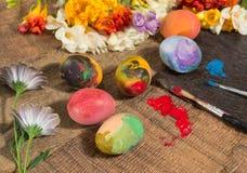 Huevos coloridos de Pascua con las flores de la primavera y los dos cepillos del pintor Foto de archivo
