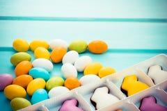 Huevos coloridos dispersados del chocolate dulce de pascua pequeños con los conejitos del caramelo en fondo azul Copyspace Foto de archivo libre de regalías