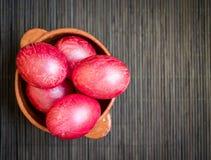 Huevos coloridos en cuenco de la arcilla Fotografía de archivo libre de regalías