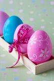 Huevos coloridos en rectángulo de madera Fotografía de archivo