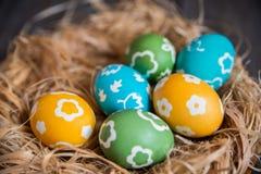 Huevos coloridos en una jerarquía de mimbre Imagen de archivo