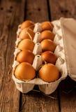 Huevos con el heno en una caja del cartón en la madera rústica Imagenes de archivo