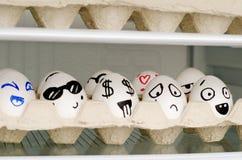 Huevos con emociones pintadas en una bandeja en un estante en el refrigerador Fotografía de archivo