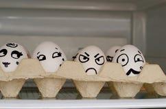 Huevos con emociones pintadas en una bandeja en un estante en el refrigerador Fotografía de archivo libre de regalías