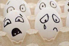 Huevos con la cara exhausta de las emociones, asustado y del griterío Imagen de archivo