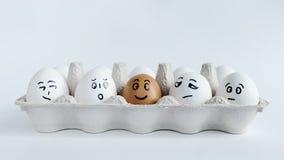 Huevos con las caras divertidas en el paquete en un fondo blanco Foto del concepto de Pascua Caras en los huevos Foto de archivo