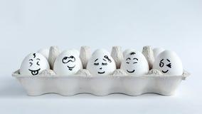 Huevos con las caras divertidas en el paquete en un fondo blanco Foto del concepto de Pascua Caras en los huevos Imagenes de archivo