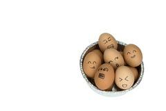 Huevos con las caras felices sonrientes en la bandeja redonda del papel de aluminio, aislada en el fondo blanco Imágenes de archivo libres de regalías