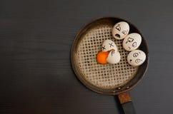 Huevos con las emociones exhaustas, huevo roto en el centro de la cacerola, tabla negra fotos de archivo libres de regalías