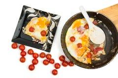 Huevos con los tomates de cereza en una cacerola Fotografía de archivo