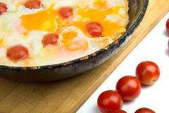 Huevos con los tomates de cereza en una cacerola Foto de archivo libre de regalías