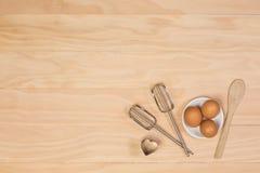 Huevos, cortador de madera de la cuchara, del batidor y de la galleta Fotos de archivo