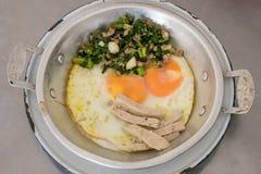 Huevos criticados deliciosos tailandeses en la pequeña cacerola de aluminio Imagenes de archivo