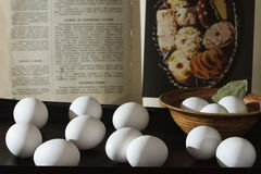 Huevos crudos con el libro de cocina, aún vida Imágenes de archivo libres de regalías