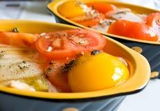 Huevos crudos con los tomates Imágenes de archivo libres de regalías
