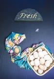 Huevos crudos en el fondo azul Foto de archivo libre de regalías