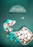 Huevos crudos en el fondo verde Imagen de archivo