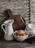 Huevos crudos en un cuenco, un jarro esmaltado, una tajadera y cuenco de cerámica en un fondo de madera oscuro rústico fotografía de archivo