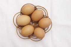 Huevos de Brown sobre una cesta de mimbre con el fondo blanco del mantel Foto de archivo libre de regalías