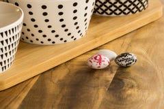 Huevos de caramelo de Pascua en superficie de madera además con de los cuencos con bla Foto de archivo libre de regalías