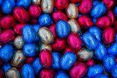 Huevos de chocolate coloreados y envueltos de pascua imágenes de archivo libres de regalías