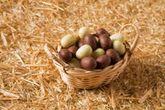 Huevos de chocolate de Pascua en una pequeña cesta Fotografía de archivo