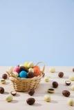 Huevos de chocolate de Pascua en una pequeña cesta con el fondo azul Fotografía de archivo libre de regalías