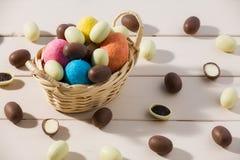Huevos de chocolate de Pascua en una pequeña cesta sobre una tabla Imagenes de archivo