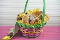 Huevos de chocolate de oro de la hoja con la decoración linda del conejito de pascua y los bollos cruzados calientes Imagen de archivo libre de regalías