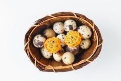 Huevos de codornices aislados en una cesta con las bolas de madera decorativas Imagen de archivo libre de regalías