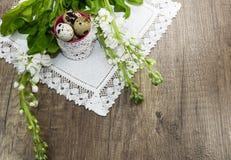 Huevos de codornices de Pascua en una servilleta de lino, flores hermosos Fotografía de archivo libre de regalías