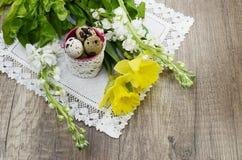 Huevos de codornices de Pascua en una servilleta de lino, narciso hermoso Foto de archivo libre de regalías