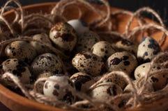 huevos de codornices en cuenco de madera en cierre azul del fondo para arriba Foto de archivo